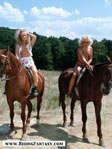 Two blond girls riding on horseback